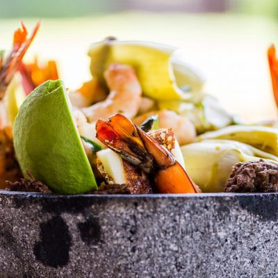 Alicia's Molcajete for Two: Experience an authentic molcajete containing chicken and beef fajitas, grilled panela cheese, shrimp, sliced avocado, artichoke hearts, filed mushrooms, poblano peppers, scallions, and topped with roasted tomatillo sauce.